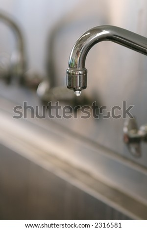 a water faucet dripping a drop of water