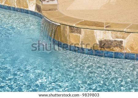 A water feature and flagstone is shown on a suburban pool - stock photo