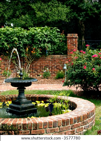 A water fountain sits in the middle of a pretty landscaped garden - stock photo
