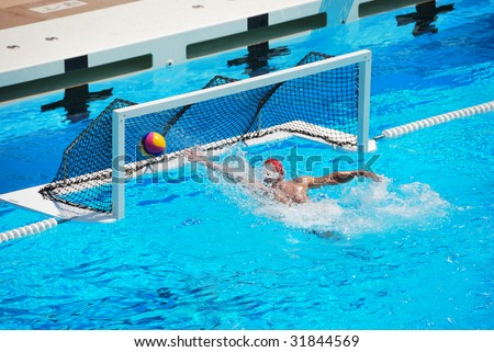 A water polo goalkeeper misses the ball going into the net of the goal. - stock photo
