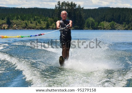 A water skier in his 60's preforming water skiing sport on a lake. - stock photo