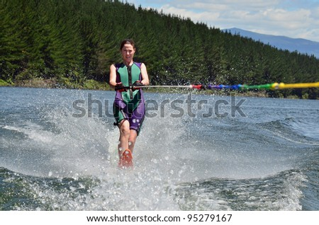 A water skier woman water skiing on a lake. - stock photo