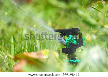 a water spray sprinkler as a tool to irrigate grass - stock photo
