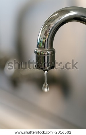 a water tap dripping a few drops of water - stock photo