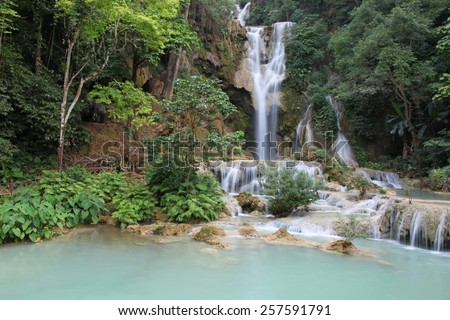 A  waterfall at the Kuang Si Falls outside of Luang Prabang. These waterfalls and cascades are a popular place for tourists and locals to visit to cool off.  Luang Prabang - Laos - stock photo