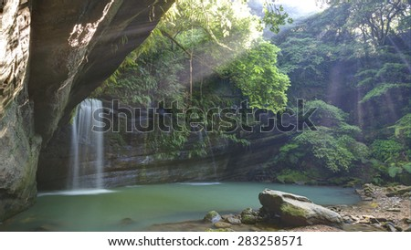 A waterfall in a mysterious forest with sunlight shining through the greenery ~ River Scenery of Taiwan - stock photo