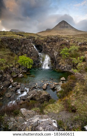 A waterfall in front of the Glennbrittle hostel at the Isle of Skye. In the background a peak of the Cuillin Hills. - stock photo