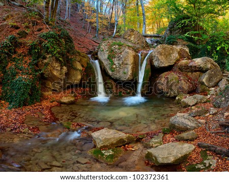 A waterfall in the mountains, around autumn forest with yellow foliage and the blue sky, outdoors - stock photo