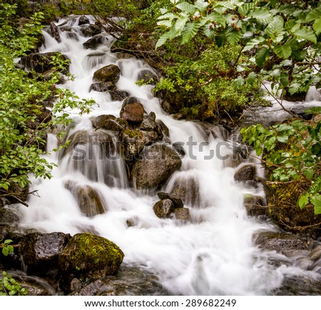 "A waterfall on the ""Trail of Time"" hiking trail at Mendenhall Glacier near Juneau, Alaska. - stock photo"