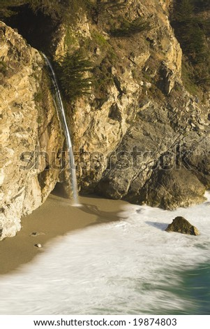 A waterfall plummets off of a cliff into the Pacific Ocean at Julia Pfeiffer Burns State Park in Big Sur, California, USA. - stock photo