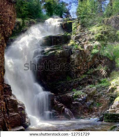 a waterfall surrounded of tropical vegetation - stock photo