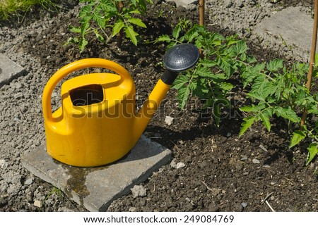 a watering can in a garden - stock photo
