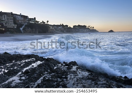 A wave begins to break along a secluded beach cove just before sunrise - stock photo