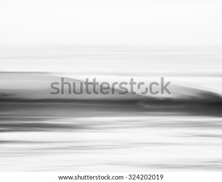 A wave breaking along the Pacific coast.  Image displays an abstract, blurred effect made using panning motion combined with a long exposure. - stock photo