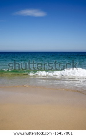 A wave breaking on Carbis Bay beach. - stock photo