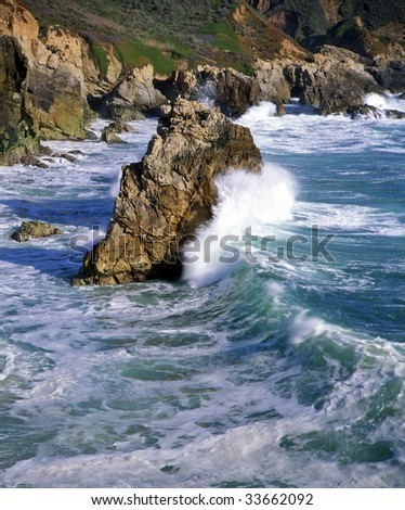 A wave crashing on a sea-stack along the Big Sur Coast of California. - stock photo