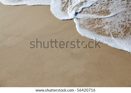 A wave rolls up the sand at the beach. Plenty of room to add your own text or design