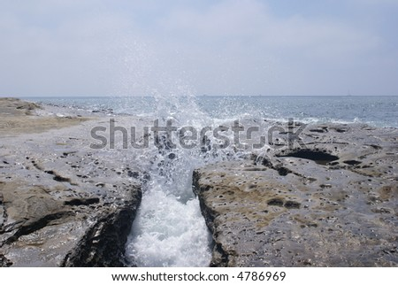 A wave splashing between to large boulders up into the air.