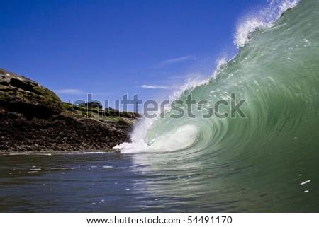 A wave throws against the rocks in Santa Cruz - stock photo