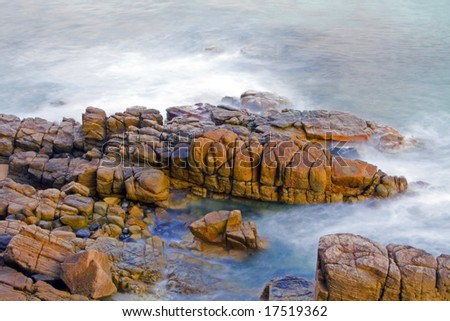 A Wave washing on rocks at sunrise using a long exposure to blur water - stock photo