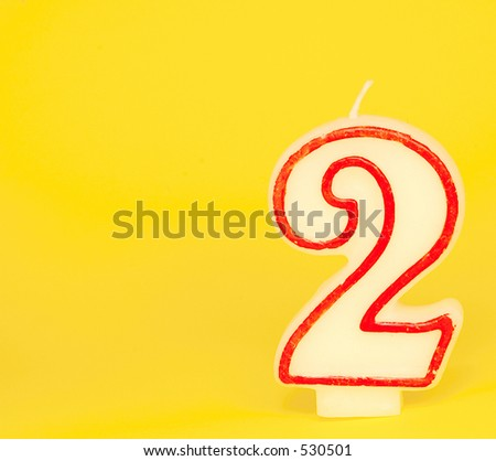 "A wax red and white candle, number ""two"" on a yellow background"
