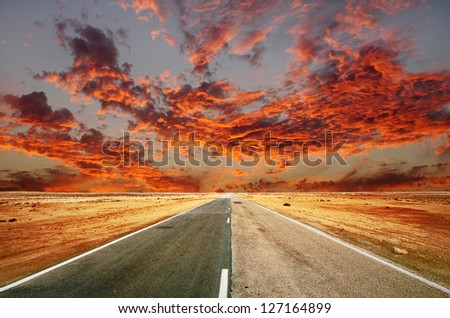 A way in the desert and dramatic clouds - stock photo