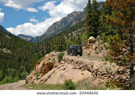 A 4WD vehicle ascending the Fall River Road in the Rocky Mountain National Park, Colorado. - stock photo