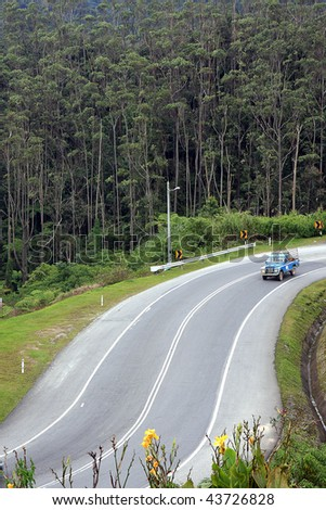 A 4WD vehicle traveling down the winding roads of Cameron Highlands, in Pahang, Malaysia. - stock photo