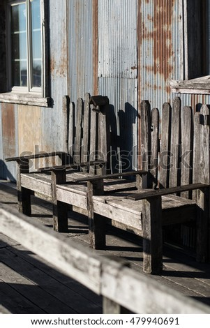 A weather worn wooden bench inviting all who pass a chance to relax while others shop in the quaint country cider store behind it.