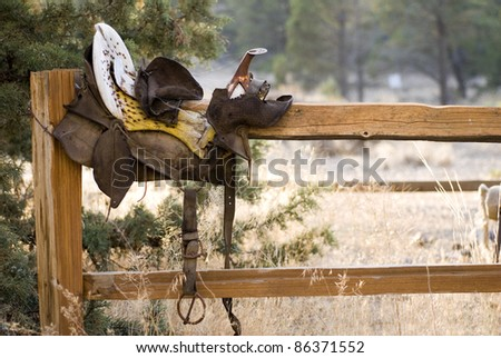 A weathered antique saddle on a split rail fence in the rural countryside.  Room for copy. - stock photo