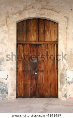 A weathered door made of distressed wood with a lock.