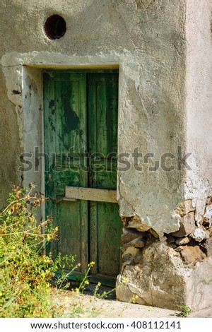 A weathered green door on the island of Panarea, Sicily, Italy.