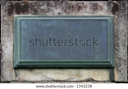 A weathered plaque embedded in a wall stone. Empty to fill in your info. - stock photo