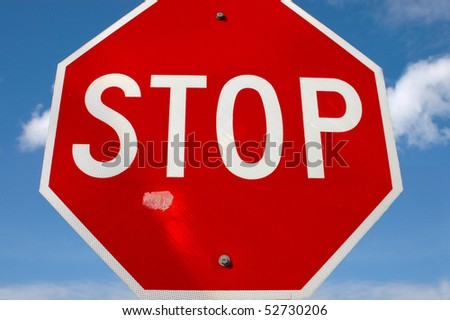 A weathered stop sign against a blue sky - stock photo