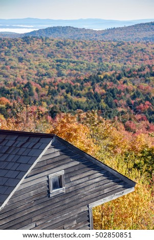 A weathered wood cabin sits at the edge of a mountain overlooking a colorful valley in Vermont