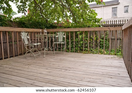 A weathered wood deck with an old iron bistro table and chairs placed in the corner, nestled in the shade of a tree in the back yard.