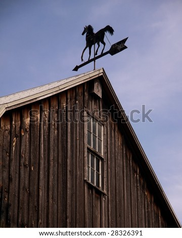 A weathervane atop a barn indicates the direction of the wind. - stock photo