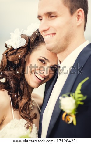 A wedding by the sea. Honeymoon. The bride and groom hugging on the shore of Lake. groom and bride hugging on a green lake. Groom and Bride in a park. wedding dress. Bridal wedding bouquet of flowers - stock photo
