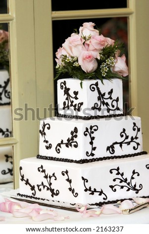 a wedding cake with pink roses sitting on a shelf with a mirror - stock photo