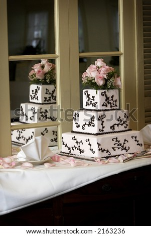 a wedding cake with pink roses sitting on a shelf with a mirror. A good place for text on the bottom right side of the photo. - stock photo