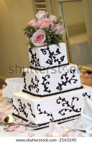 a wedding cake with pink roses. very shallow depth of field - stock photo
