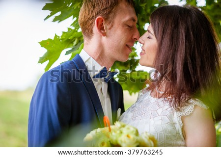 a wedding couple kissing  in park, summer