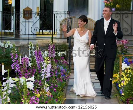 A wedding couple walk down the aisle - stock photo