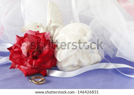 a wedding favors and wedding ring on colored backrgound - stock photo