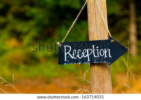 A wedding reception sign is made from a small chalkboard and has been outside in the rain. The sign is an arrow hung with twine. - stock photo