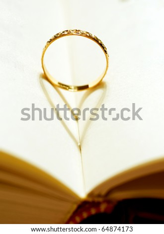 A wedding Ring in the book with shadow of heart shape - stock photo