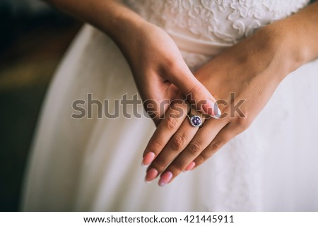 A wedding ring on the finger of the bride. - stock photo