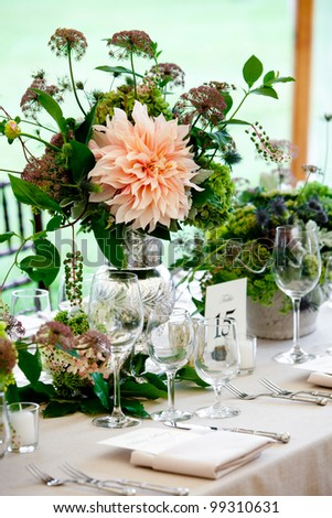 a wedding table set for fine dining with a pretty flower centerpiece - stock photo