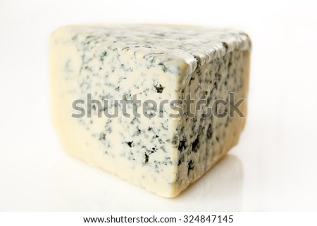 A wedge of Roquefort or blue cheese on a reflective surface.