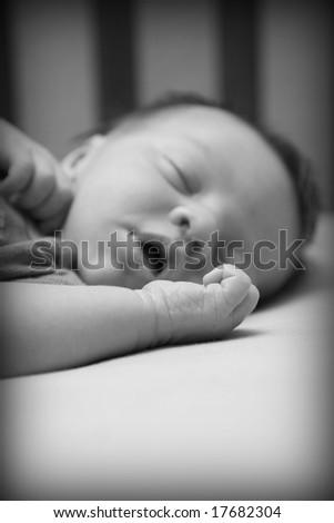 A week old baby in a crib. Shallow DOF
